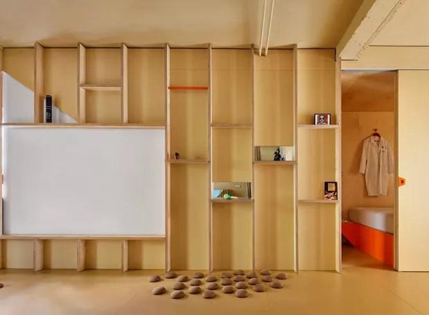Um painel de madeira forma a divisória entre a sala e o quarto, que fica separado por uma porta de correr (Foto: José Hevia./ Dezeen)
