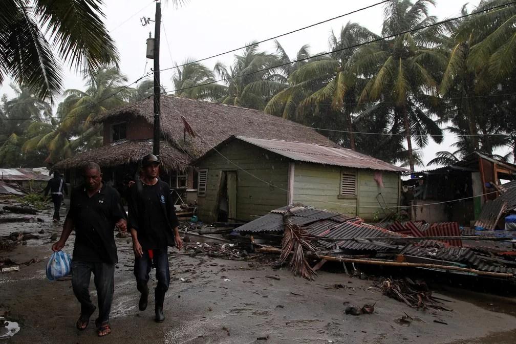 Homens atravessam uma casa destruída pela passagem do furacão Irma, em Nagua, República Dominicana (Foto: Ricardo Rojas/Reuters)