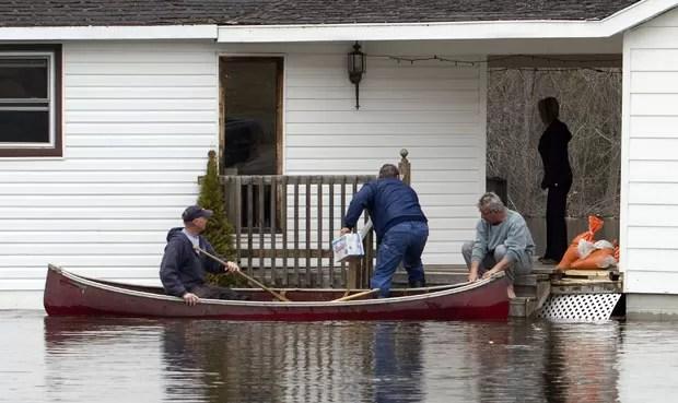 Moradores usam canoa para levar cerveja para vizinho ilhado por inundação (Foto: Fred Thornhill/Reuters)