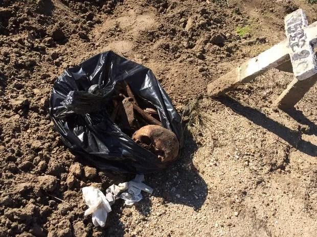 Sacos pretos com ossadas são vistos ao lado de covas no cemitério do Murundu, em Realengo (Foto: Janaína Carvalho / G1)