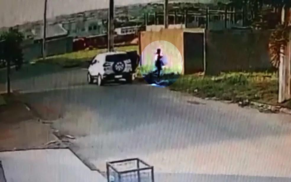 Momento em que, segundo polícia, mãe leva bebê em caixa de papelão para ser queimado em lote de Anápolis — Foto: Divulgação\Polícia Civil