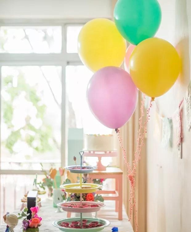 A mesa do bolo, de frente pra um janelão, ganhou destaque na festa. No cordão das bexigas, grelots cor-de-rosa (Foto: Carina Iwahashi/Editora Globo)