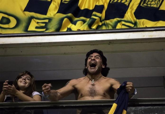 Diego Maradona grita sem camisa da arquibancada celebrando um gol do Boca Juniors sobre o Unión Maracaibo em jogo pela Copa Libertadores da América em abril de 2008, em Buenos Aires — Foto: Natacha Pisarenko/AP/Arquivo