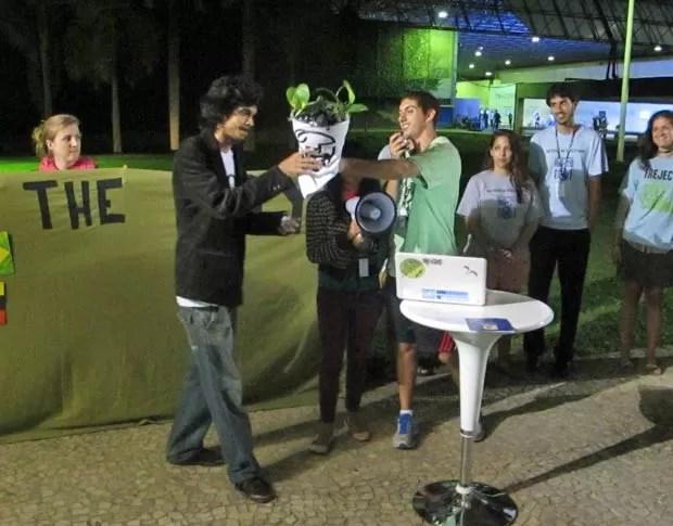 Jovem representando o Brasil recebe o troféu do 'Fóssil do Dia' na cerimônia organizada pelas ONGs. (Foto: Dennis Barbosa/G1)