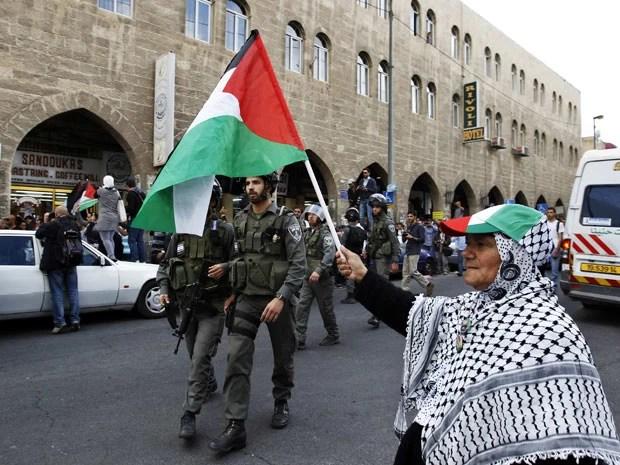 Senhora segura bandeira palestina no centro velho de Jerusalém, em protesto a criação do Estado hebreu (Foto: Reuters)