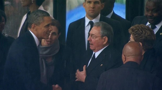 Observado por Dilma, os presidentes dos EUA, Barack Obama, e de Cuba, Raúl Castro, se cumprimentam nesta terça-feira (10) em homenagem a Mandela (Foto: Reuters)