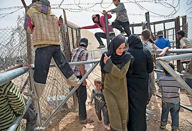 Um grupo tenta obter suprimentos em Zaatari, na Jordânia (Foto: Lynsey Addario/The New York Times)