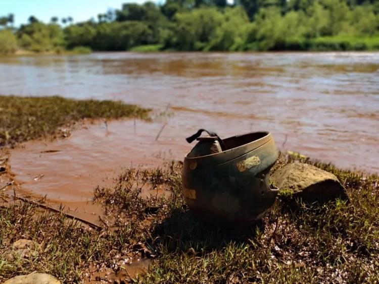 Ás margens do rio, capacete que desceu com a enxurrada — Foto: Paula Paiva Paulo