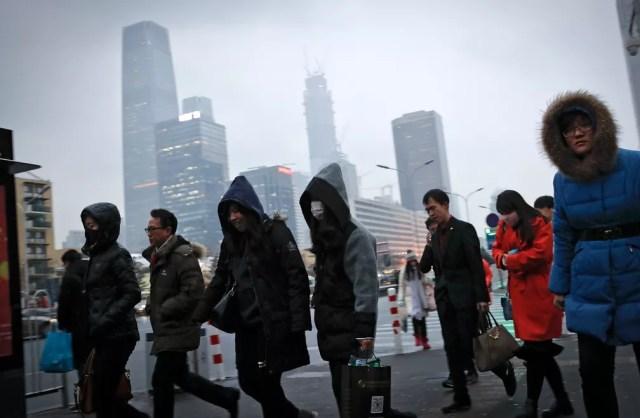 Foto de 21 de fevereiro de 2017 mostra moradores de Pequim caminhando em direção a uma estação de metrô, sob céu cinzento de poluição (Foto: AP Photo/Andy Wong)
