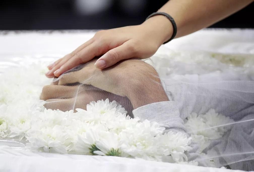 Uma pessoa toca as mãos de uma das vítimas do massacre na Escola Estadual Raul Brasil, em Suzano, durante velório nesta quinta-feira (14). Os corpos de seis vítimas foram velados no local — Foto: Ueslei Marcelino/Reuters