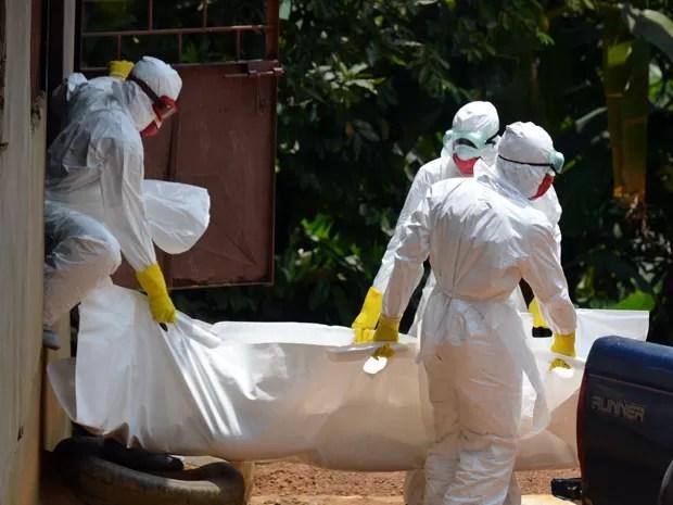 Traabalhadores da Cruz Vermelha usando roupa especial carregam o corpo de uma vítima do vírus ebola em 12 de setembro em Monróvia, na Libéria (Foto: AFP Photo/Zoom Dosso)