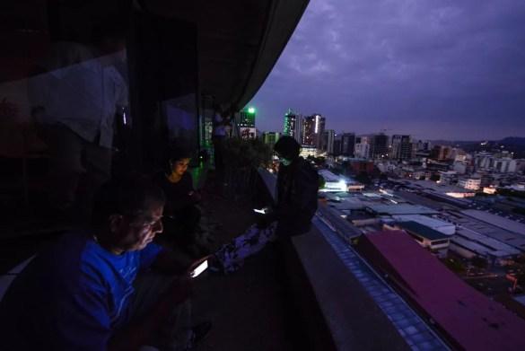 Pessoas usam celulares no primeiro dia de apagão em Caracas, em 7 de março — Foto: Matias Delacroix/AFP