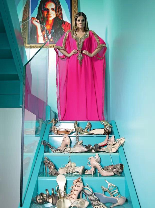 Na escadaria que leva ao closet que construiu sobre a sua suíte, Thássia posa com caftã comprado em Dubai e uma fração de sua coleção de sapatos (Foto: Raphael B)