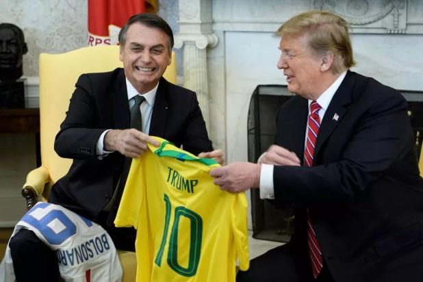 O presidente Jair Bolsonaro entrega camisa da Seleção Brasileira de futebol para Donald Trump; presidente norte-americano também presenteou Bolsonaro — Foto: Brendan Smialowski / AFP