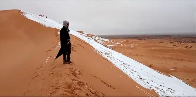 Homem olha para duna coberta de neve no deserto do Saara, na cidade de Ain Sefra, Argélia (Foto: Hamouda Ben Jerad/via Reuters)