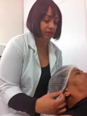 Carla Gomes, fazendo limpeza na pele de uma cliente, em Brasília (Foto: Raquel Morais/G1)