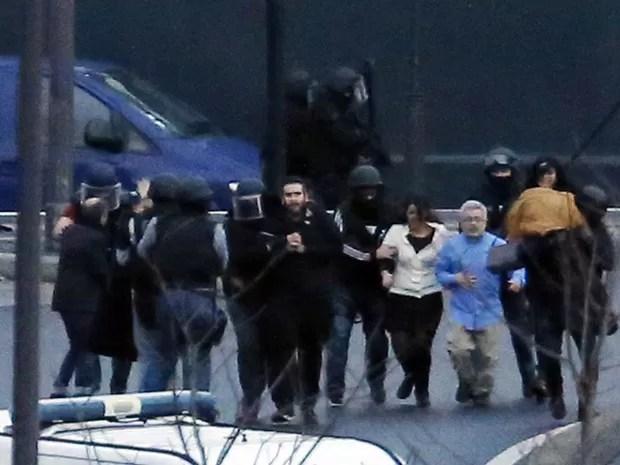 Diversos reféns são retirados pela polícia de mercado kosher em Paris (Foto: Thomas Samson/AFP)