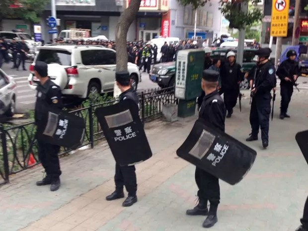 Policiais montam guarda perto do local da explosão, no centro de Urumqi (Foto: Cao Zhiheng/AP Photo)