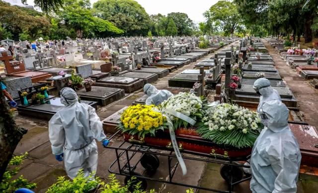 Coveiros carregam caixão de vítima da Covid-19 em cemitério municipal de Porto Alegre, no dia 26 de março. — Foto: Silvio Avila/AFP