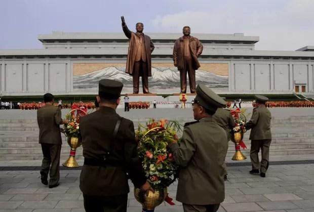 Soldados norte-coreanos levam flores às estátuas de Kim Il Sung e Kim Jong Il para marcar o 20º aniversário da morte do primeiro nesta terça-feira (8) (Foto: Kim Kwang Hyon/AP)