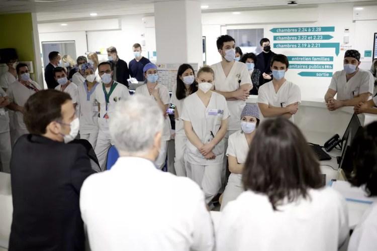 O presidente da França, Emmanuel Macron, conversa com profissionais de saúde da UTI em hospital perto de Paris na quarta (17) — Foto: Yoan Valat/Pool via AP