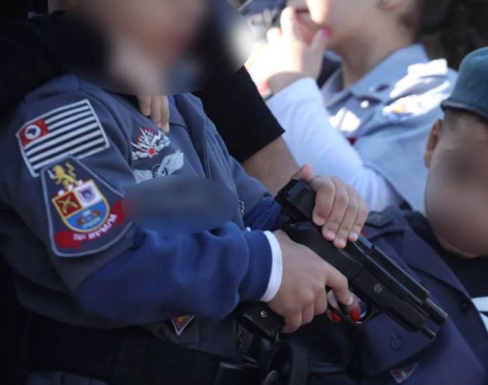 Criança fardada segura arma de brinquedo durante desfile de 9 de julho em SP  — Foto: Renato Cerqueira/ Futura Press/ Estadão Conteúdo