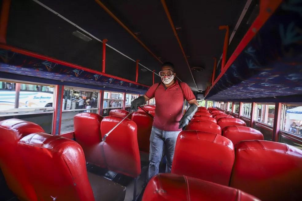 Com máscara, homem desinfeta ônibus para prevenir contágio do novo coronavírus em Manágua, na Nicarágua, em foto de 7 de abril — Foto: Alfredo Zuniga/AP Photo