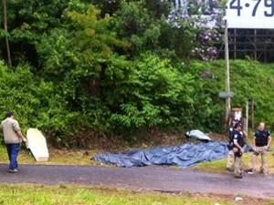 Corpos dos mortos retirados do ônibus são ensacados e levados para local próximo onde depois seguirão (Foto: Giovana Sanchez / G1)