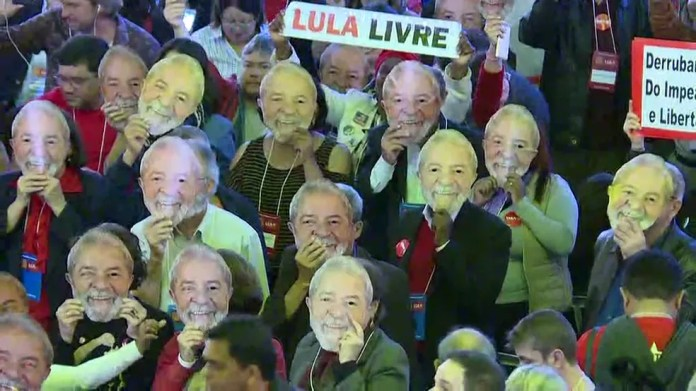 Durante convenção nacional do PT, militantes usam máscara com foto de Lula (Foto: GloboNews/reprodução)