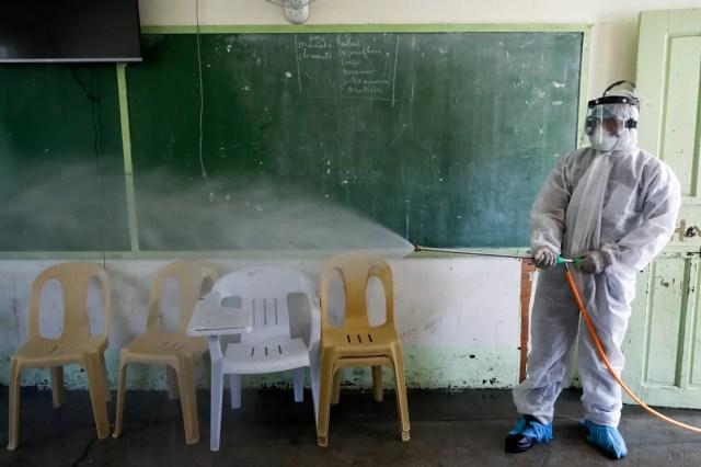 Um trabalhador desinfeta uma sala de aula dentro de uma escola, seguindo uma ordem do governo local em meio a novos casos de coronavírus no país, em San Juan, região metropolitana de Manila, nas Filipinas — Foto: Reuters/Eloisa Lopez