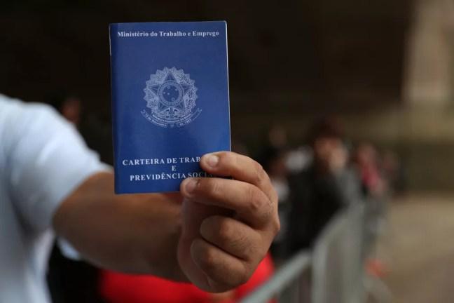 Trabalhador segura carteira de trabalho — Foto: Amanda Perobelli/Reuters