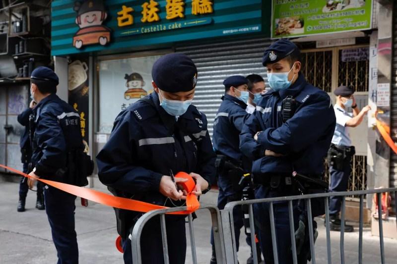 Policiais do lado de fora do escritório de Daniel Wong Kwok-tung, advogado especialista em direitos humanos e ativista pró-democracia em Hong Kong — Foto: Tyrone Siu/Reuters