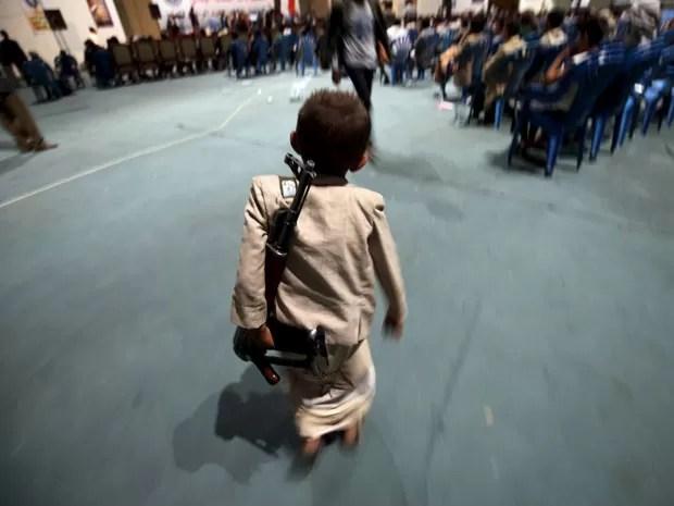 Menino carrega rifle durante comemoração do 25º aniversário de unificação do Iêmen (Foto: Mohamed al-Sayaghi/Reuters)