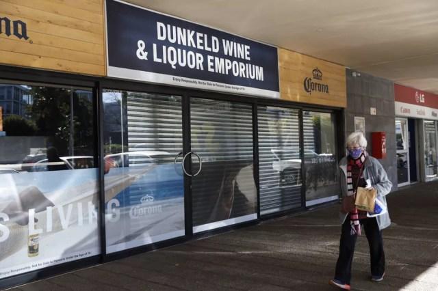 Mulher caminha por centro comercial, diante de lojas que vendem bebidas alcóolicas totalmente fechadas, em Johanesburgo — Foto: Michele Spatari/AFP