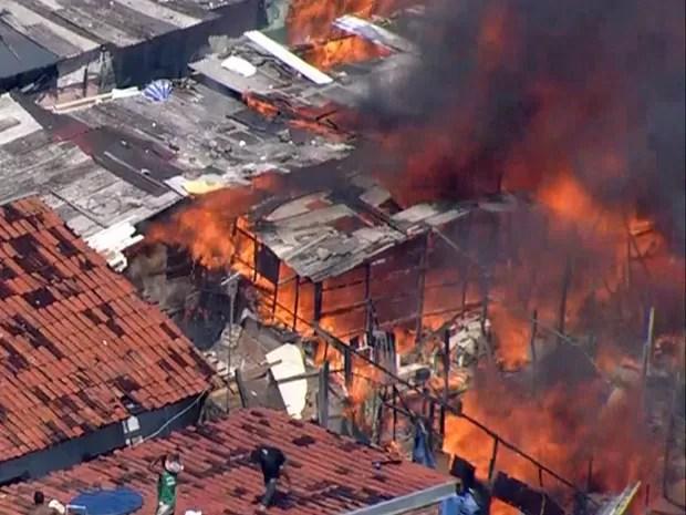 Moradores tentam apagar as chamas com água de caixa d'água (Foto: Reprodução / TV Globo)