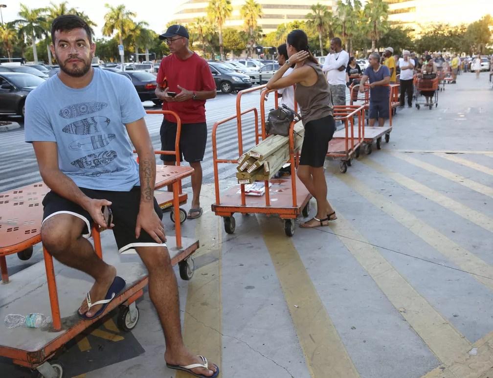 Max Gracia aguarda em uma fila para comprar folhas de madeira para proteger construções dos impactos do furacão Irma (Foto: AP Photo/Marta Lavandier)