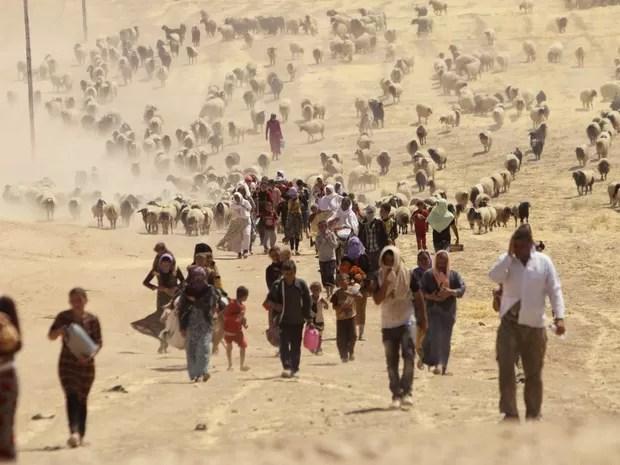 Iraquianos desabrigados da minoria Yazidi caminham para a fronteira com a Síria após abandonarem suas casas para fugir da violência na cidade de Sinjar. Militantes do Estado Islâmico mataram ao menos 500 membros da etnia em ofensiva no norte do Iraque (Foto: Rodi Said/Reuters)