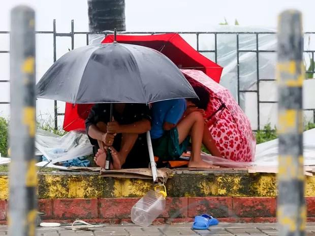 Pessoas tentam se abrigar dos ventos e da chuva em Manila neste domingo (18) (Foto: AP Photo/Bullit Marquez)