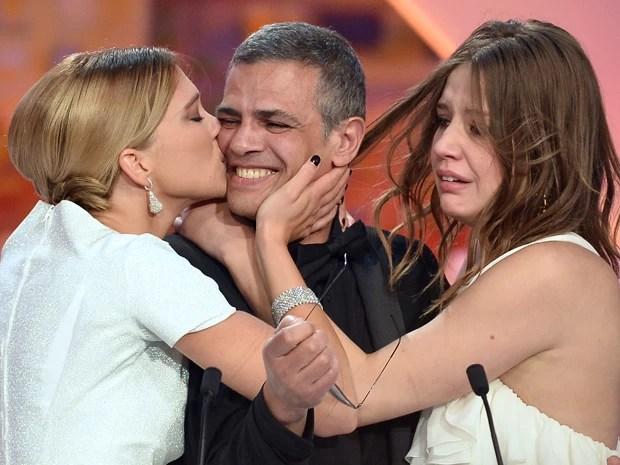 A atriz Lea Seydoux beija o diretor franco-tunisiano Abdellatif Kechiche, ao lado da atriz Adele Exarchopoulos, após o anúncio de que o filme protagonizado por ela e dirigido pelo cineasta ganhou a Palma de Ouro em Cannes (Foto: Alberto Pizzoli / AFP)