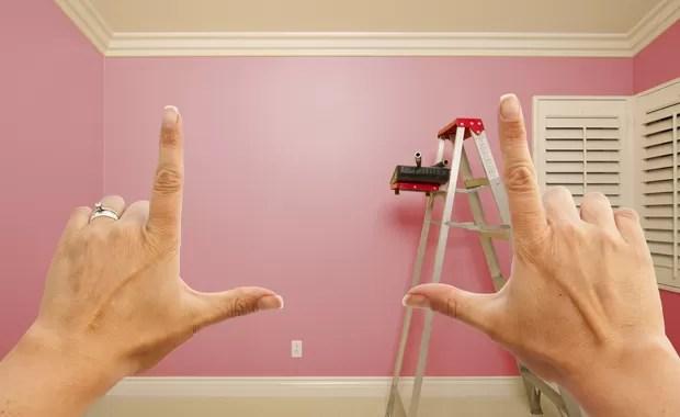 Mãos apontando para o quarto do bebê em reforma (Foto: Shutterstock)