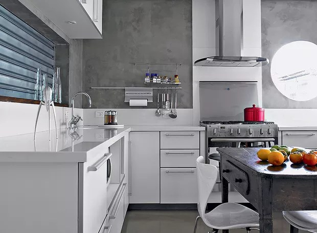 A cozinha foi revestida de Tecnocimento e tem móveis brancos, que ajudam a clarear o ambiente. Projeto da arquiteta Claudia Haguiara (Foto: Christian Maldonado/Casa e Jardim)