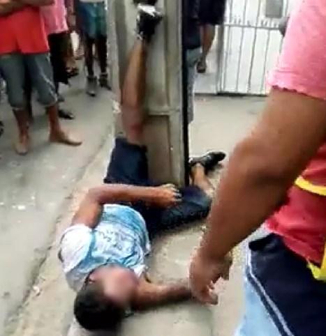 Suspeito de assalto foi amarrado em um poste (Foto: Reprodução/G1)
