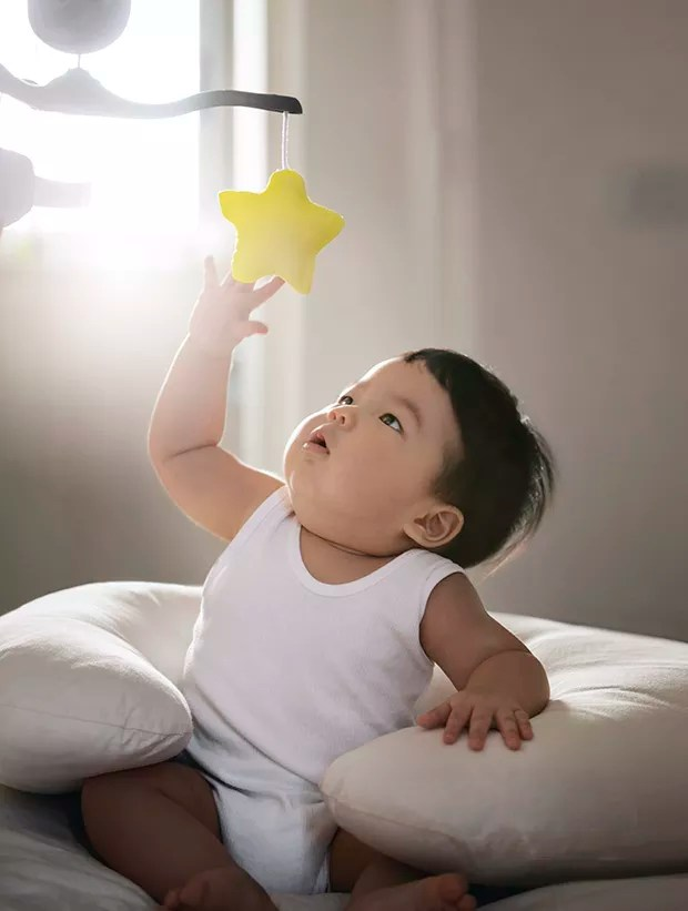 "Asian toddler boy sitting on bed reaching out to catch a rotating toy star. Conceptual baby photo, ""Reaching out to the star"". (Foto: Getty Images)"