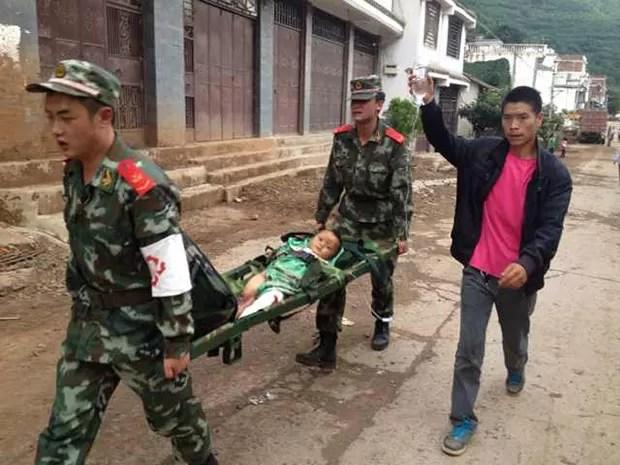 Equipes de resgate carregam criança ferida em terremoto em Zhaotong, na China, neste domingo (3) (Foto: AFP)