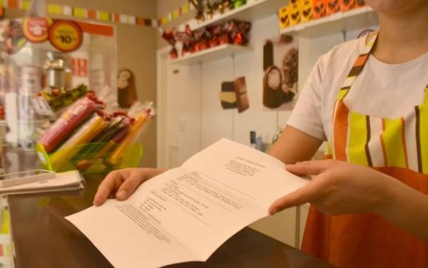 Funcionária recebe currículo para trabalho temporário em loja de chocolates em Campinas (Foto: Clara Rios/G1)