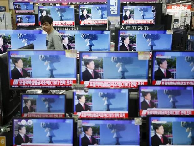 Em uma loja de Seul, capital da Coreia do Sul, vendedor passa entre televisores noticiando o suposto teste nuclear com bomba de nitrogênio realizado pela Coreia do Norte perto da fronteira com seu vizinho do sul (Foto: Kim Hong-ji/Reuters)