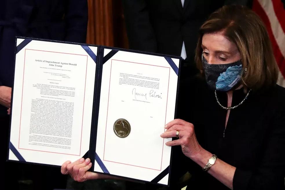 A presidente da Câmara dos EUA, Nancy Pelosi, exibe documento do segundo impeachment de Trump — Foto: Reuters/Leah Millis TPX
