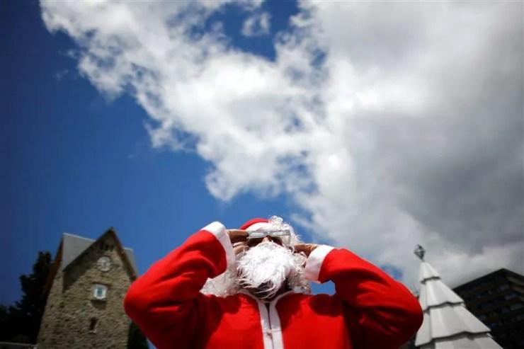 Homem vestido de Papai Noel usa óculos de proteção especiais para observar o eclipse nesta segunda-feira (14) em Bariloche, na Argentina. — Foto: Carlos Barria/Reuters