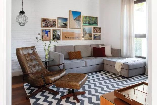 Na sala de TV projetada pela arquiteta Luciana Galves, os quadros estão alinhados na altura do sofá. As fotografias de viagem tiradas pelos moradores têm a mesma paleta de cores (Foto: Cacá Bratke / Divulgação)