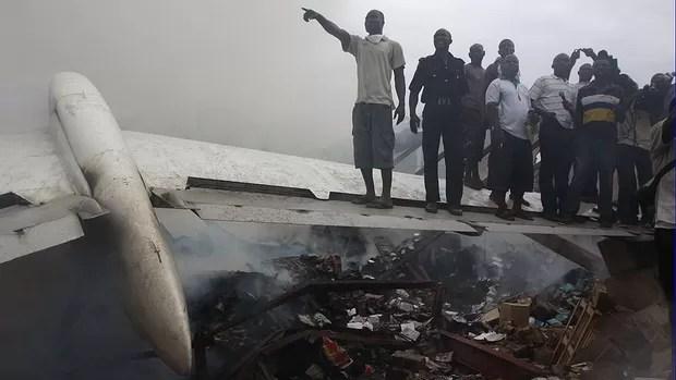 Moradores do local do acidente sobem numa das asas do avião que caiu em Lagos, na Nigéria (Foto: Sunday Alamba/AP)